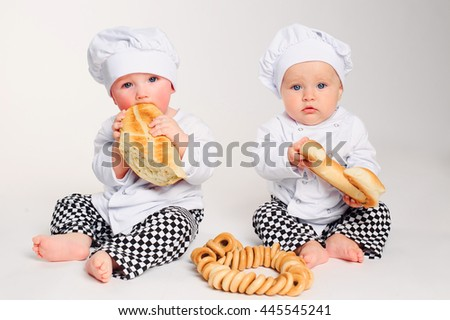 Happy little kids with chef hats eating fresh bread and pastry. Studio shot. - stock photo