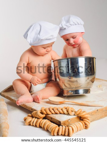 Happy little kids with chef hats preparing a cake or pizza dough, mixing ingredients. Studio shot with kitchen tools and flour.