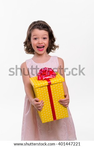 Happy little model looks in camera and shows all of her joy after getting a beautiful present box with intriguing gift. Studio photo shoot. - stock photo