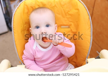Happy little 7 months baby girl on baby chair in kitchen