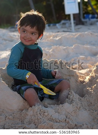 Happy little playing on white sand beach with his toy shovel