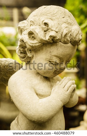 happy little praying cupid sculpture in the garden in vintage style decoration