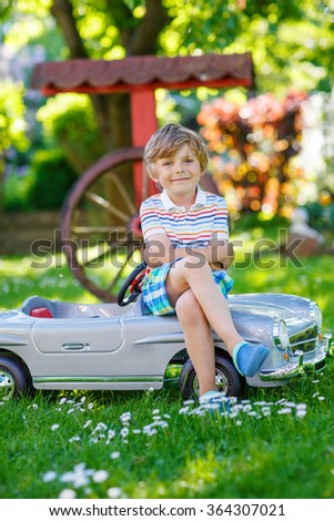 Happy little preschool kid boy driving big toy old vintage car and having fun, outdoors. Active leisure with children during school holidays on warm summer sunny day. - stock photo