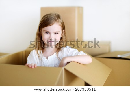 Happy little preschooler girl having fun playing with a cardboxes while moving in her new home - stock photo