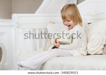 Happy little pretty girl with gift box sits on a sofa in the room. Birthday. - stock photo