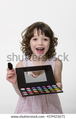 Happy little princess holds professional palette with colorful eye shadows, mirror and brush. Qualitative beauty product. Opened mouth and fire in her eyes shows her true attitude. - stock photo