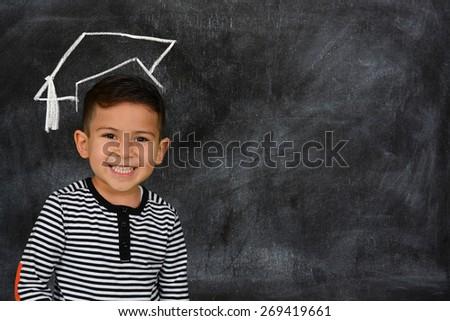 Happy little schoolboy posing in front of black chalkboard - stock photo
