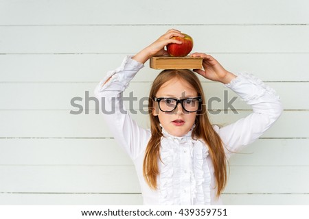 Happy little schoolgirl with book and red apple on her head, wearing white vintage blouse and black frame eyeglasses, standing against white wooden background. Back to school concept - stock photo