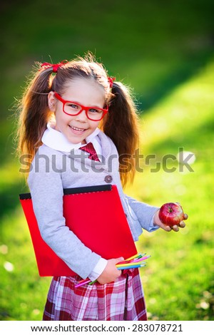 Happy little schoolgirl with lunch, book and pencils. Back to school outdoor - stock photo