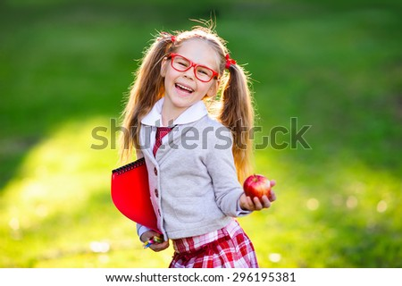 Happy little schoolgirl with notes and pencils going back to school outdoor - stock photo