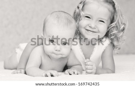 happy little sister hugging her brother lying ( black and white ) - stock photo