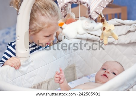 happy little sister looks into the cradle to the newborn brother