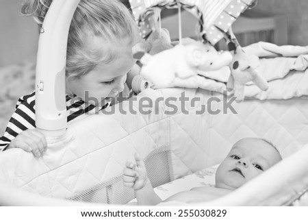 happy little sister looks into the cradle to the newborn brother  ( black and white )
