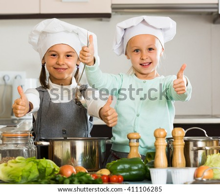 Happy little sisters in caps learning how to cook at home kitchen
