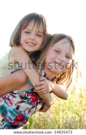 Happy little sisters on green summer meadow background - stock photo