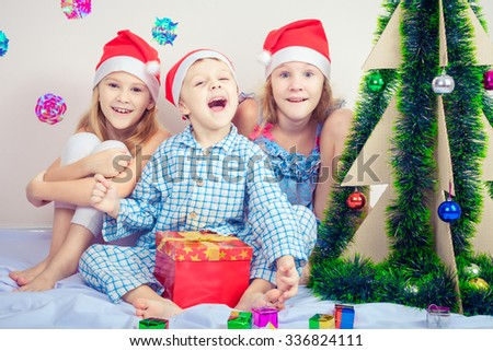 Happy little smiling boy and two girls with christmas hat. Concept of happy merry christmas.