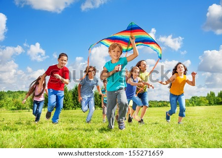 Happy little smiling boy with kite running in the park with kite and group of friends in the park on sunny summer day