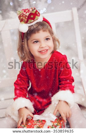 Happy little smiling girl with christmas gift box - stock photo