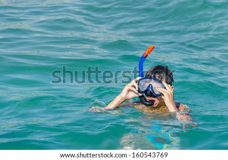 Happy Little Snorkeler. Portrait of happy little boy with an underwater mask in the swimming pool on summer day. - stock photo