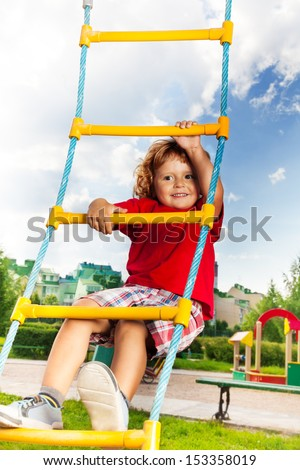 Happy little three years old child boy climbing on the rope ladder with sky on background - stock photo
