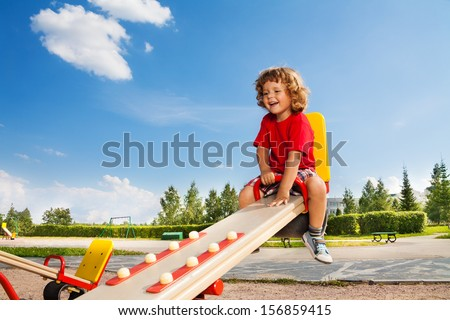 Happy little three years old child riding seesaw with big smile and happy face - stock photo