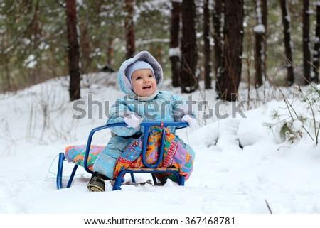 Happy little toddler boy in warm overalls sitting on the sledge in the winter forest, outdoor portrait, family spending time outdoors - stock photo