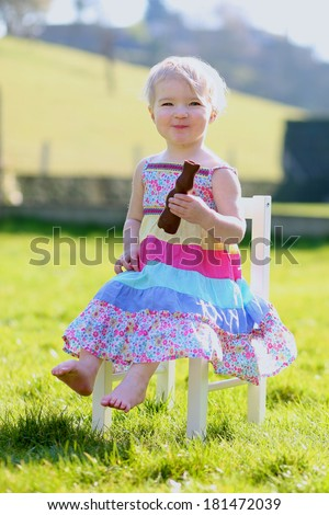 Happy little toddler girl in beautiful floral dress eating tasty chocolate bunny sitting outdoors in the garden on a sunny Easter day  - stock photo