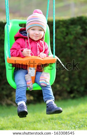 Happy little toddler girl playing outdoors on the swing - stock photo