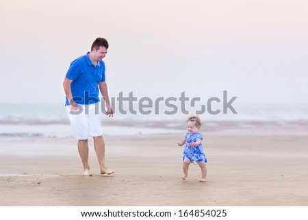 Happy little toddler girl running at a beach with her father at sunset