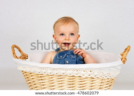 Happy little toddler sitting in the wicker basket