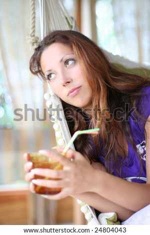 happy long-haired girl drinking lemonade in comfortable cottage - stock photo