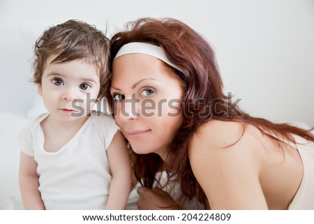happy-looking baby and  beautiful mother playing together on the bed - stock photo