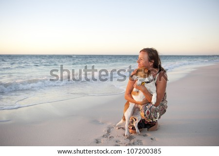 Happy looking mature woman is enjoying a sunset at the beach with her pet dog, with ocean and twilight sky as background and copy space. - stock photo