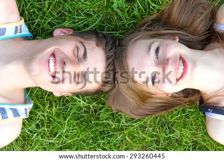 Happy love couple lying in the grass - stock photo