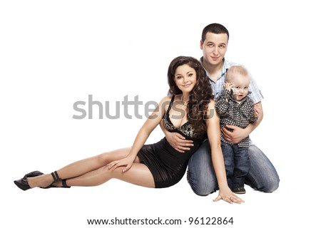 Happy love family with child - mother and father hug their son, posing on white background in studio closeup