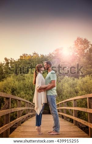 happy lovely couple on sunset bridge - stock photo