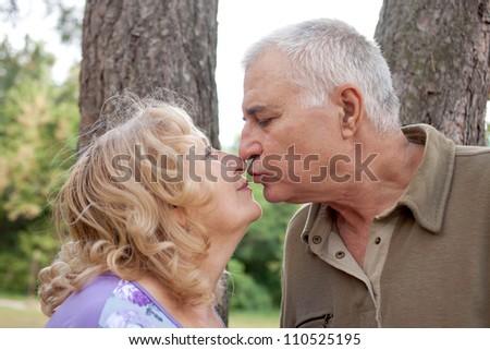 Happy lovely elderly senior couple kissing in park. Summer holiday. - stock photo