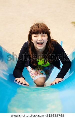 Happy lovely girl on a children's slide on playground - stock photo