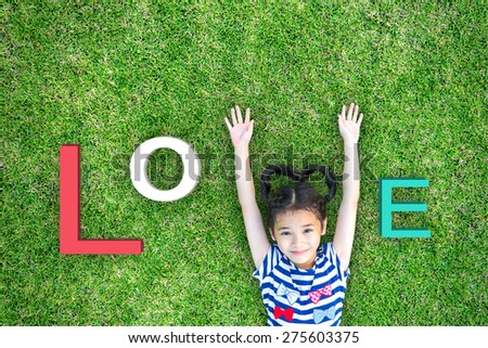 Happy lovely kid raising two hands on grass lawn with alphabet letters together read word love: Little girl having fun time activity raising hand posture: Child love hygiene eco clean environment csr - stock photo