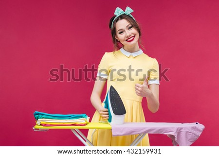 Happy lovely pinup girl ironing clothes and showing thumbs up over pink background - stock photo