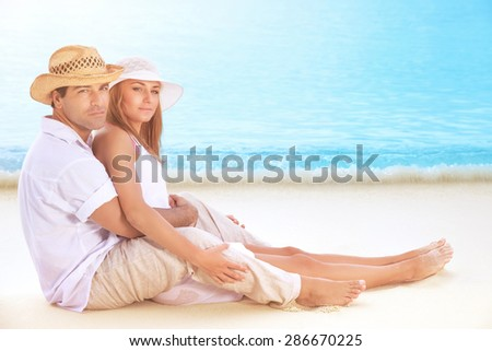 Happy lovers on the beach, beautiful young couple sitting on sandy coast and hugging, enjoying each other and romantic honeymoon vacation - stock photo