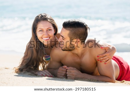 Happy lovers resting on sandy beach at vacation together - stock photo