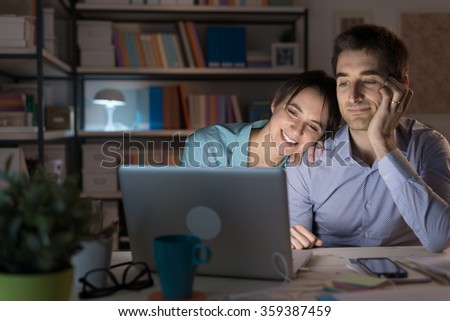 Happy loving couple at home, sitting at desk and using a laptop they are watching videos online and networking, she is leaning on her husband's shoulder - stock photo