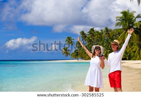 happy loving couple drinking wine at tropical beach - stock photo