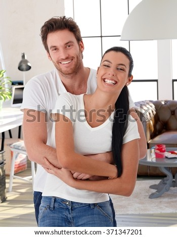 Happy loving couple embracing at home, laughing, looking at camera. - stock photo