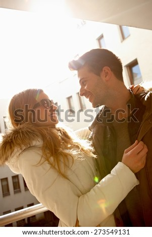 Happy loving couple embracing at wintertime in sunlight. - stock photo