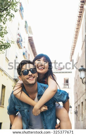 Happy loving couple. Happy young man piggybacking his girlfriend while hug he - stock photo