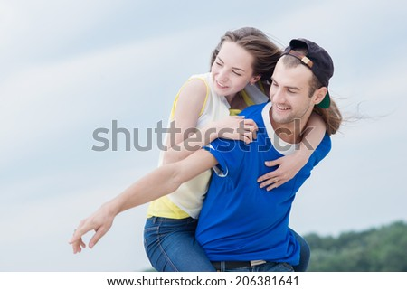 Happy loving couple having fun on the beach. The girl jumped on the back guy. - stock photo