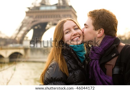 Happy loving couple in Paris, kissing by the Eiffel Tower - stock photo