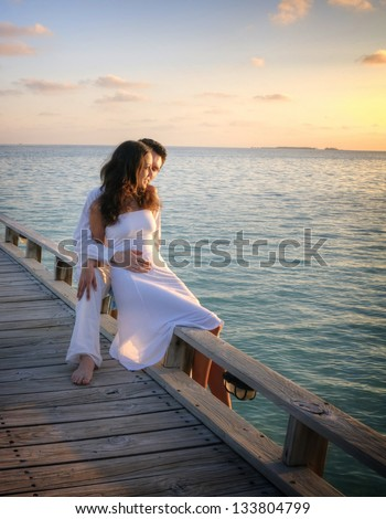 Happy loving couple in white clothes posing on a pier on Maldives - stock photo